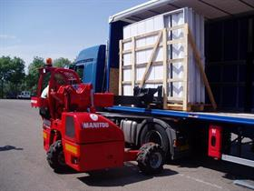 A Manitou truck-mounted forklift loading glass onto a truck.